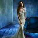 Style tk2157 Ivory lace trumpet bridal gown with deep sweetheart neckline, floral applique at empire waist and spaghetti straps. Sparkle tulle underlay, chapel train. Lace bolero with floral applique. Available in Ivory and White.