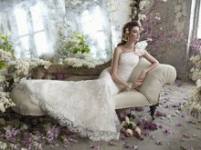 StyleTK2250 Ivory Alencon lace one shoulder trumpet bridal gown with floral detail, sweep train with organza petals.