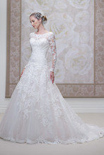 Style #J11455 <br /> Lace and tulle ball gown with scalloped lace sheer curved bateau neckline and long sleeves, sweetheart bodice with dropped waistline, deep plunging scalloped back bodice finished with covered buttons, full skirt with scalloped hemline and chapel length train.