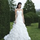 Style #3727 A drop waist ruffle ball gown with asymmetric draped organza and a sweetheart neckline. Buttons cover the back zipper and this style has a semi-chapel length train.