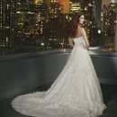 9700 A sweetheart neckline lace A-line with a beaded belt featuring pearls, sequins, crystals and bugle beads. Lace appliques on tulle over an all over lace. Buttons over the back zipper to the end of the chapel length train.