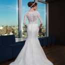 Style # 9754 Hand beaded Alencon lace over satin trumpet gown featuring a jewel neckline, three quarter length sleeves and an attached pearl belt that highlights the natural waist. The gown is finished with tulle covered buttons to the back of the godet and a semi-chapel length train.