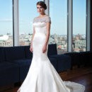 Style 9735 Silk cotton satin mermaid silhouette features a heavily beaded illusion scoop neckline and cap sleeves. The beading continues throughout the illusion back neckline and jeweled and fabric buttons trail down the chapel length train. (Available in silk dupion as 9742)