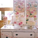 Vintage buffet with 5 cakes with vintage shutters covered in garden roses for a backdrop.
