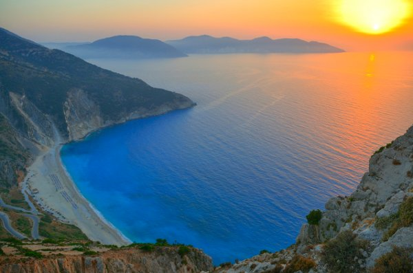 Remarkable sunset over the beautiful beach of Myrtos, Kefalonia, Greece. One of the many romantic experiences of a honeymoon in Greece.