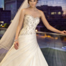 D1425 This stunning and sophisticated Luxe Taffeta designer bridal gown features intricate, hand-sewn Swarovski crystal embellishments on its sweetheart bodice and figure-flattering asymmetrical pleating at the waist. Skirt flows full into a chapel train. Lace up or zipper back available.