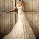 D1319 Tiered ruffles of Royal Organza and lace curve the body and then flow gently from the scoop neck to the scalloped hem on this glamorous A-line designer wedding gown. The chapel train adds vintage glamour. Choose from a lace up or zipper back closure.