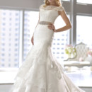 D1523 This Royal Organza and lace trumpet wedding gown comes with a cap-sleeve lace jacket and features tiers of lace trim on its skirt. Available in lace up or zip up and with or without lace jacket. Beaded Grosgrain ribbon sash with Diamante embellishments sold separately.