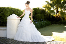 D1199 This voluminous ball gown is accented with Swarovski crystal trim and an asymmetrical shoulder strap. Billowy Soft Organza fabric pickups on the skirt add a whimsical touch. Chapel train. Lace up or zipper back available.