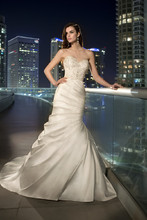 D1459 This strapless designer wedding dress is made from exquisite Dolce Satin and features a trumpet silhouette with gorgeous fan pleating on the skirt. The completely beaded crystal bodice adds modern flair for the bride who loves to sparkle. Lace up or zipper back available. Grosgrain ribbon sash sold separately.