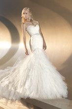 D1463 This whimsical designer fit-and-flare wedding gown features a bodice with soft lace under tulle and a skirt that blooms with tiered layers down to a court train. Detachable Swarovski crystal beaded sash accentuates the waist. Lace up or zipper back available.