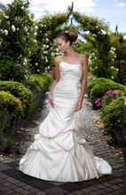 D1129 This Dolce Satin designer wedding gown features a mermaid silhouette with beading under the bust, a ruched bodice, and whimsical fabric pickups on the skirt. Chapel train. Lace up or zipper back available.