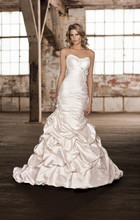 D1271 This Luxe Taffeta fit and flare designer wedding gown features a ruched sweetheart bodice, pick-up style skirt and chapel train. Diamante accentuates the floral details, which can be found at the waist and hip. Lace up or zipper back available.