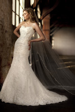 D1273 This head turning lace and Luxe Taffeta designer wedding gown features an overlay of dotted Swiss lace with intricate floral embellishments, a sweetheart neckline, dropped waist, and an elegant chapel train. Lace up or zipper back available.