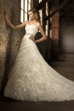 D1308 Unique and beautiful, this Soft Organza bridal gown features a ruffled neckline, ruched bodice, full skirt with textured organza inset, and a dramatic jewel encrusted detachable belt. Choose from lace up or zipper back. Chapel train.