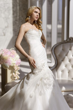 D1539 This trumpet silhouette designer wedding gown is made of whispery-soft Royal Organza and features asymmetrical pleating on the bodice, Diamante details along the sweetheart neckline, waist and skirt, and a delicate floral and petal motif on the skirt. Available in lace up or zip up.