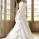 5762 When you walk the aisle in this strapless French Mikado gown, you'll feel like you're walking the Red Carpet. This designer gown boasts a natural waistline that's accentuated with exquisite crystal detailing. Fun and flirty hip draping design completes the fashion forward look.