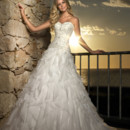 5671 This designer A-line Organza gown with ornately beaded bodice and full, flowing skirt is positively stunning. The skirt is accented with ruffles that will sway as you make your way down the aisle.