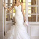 Style 5835 - This trumpet designer bridal gown features asymmetrical Organza pleats throughout its beautiful bodice and skirt, while fun and flirty gathered fabric on the side hints at vintage charm.