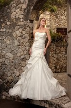 5600 Add sophistication and glamour to your wedding day in this soft crushed Taffeta fit and flare gown. This dress offers loose ruching throughout the bodice and is accented by pickups that gracefully cascade down to a full skirt. The gown in finished with a small delicate cluster of flowers adorning a figure-flattering, detachable belt.