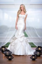 5549 This chic, Dolce Satin fit and flare gown is completed with Diamante and Lace accents. It is designed with a soft, figure-flattering ruching throughout the bodice and has powerful and shapely pickups to create a cascading and dramatic skirt. Bridal gown also comes with a detachable one-shoulder strap.