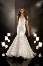 338 Designer fit-and-flare bridal gown features a detachable hand-tailored silk rosette sash, dramatic, textured pleating on the skirt, and a smooth, body-hugging sweetheart bodice. Lace up or zipper back available.