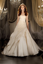 412 Designer wedding ball gown features a ruched bodice with a sweetheart neckline and a full, flowing skirt with structured folds. Optional beaded lace belt defines the waist.