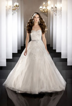 457 Strapless tulle bridal ball gown features Venice lace appliqués layered within the fabric, a sweetheart neckline, covered buttons and a chapel train. Waist is detailed with Valencia Satin ribbon belt with Swarovski Crystal beaded floral details