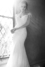 Style 624  Lace over Lustre Satin fit-and-flare designer bridal gown from the Martina Liana wedding gown collection features hand-sewn crystals and a frothy court train. The cap sleeves draw attention to your face and add stylish functionality.The back zips up under crystal buttons.
