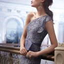 Style 3227  <br />Graphite alencon lace dress, one shoulder neckline with ruffle cascade at side, organza tie sash at natural waist, pencil skirt.