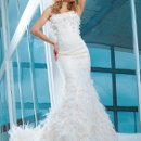 Style No. T112244 Strapless soft lace and tulle over satin mermaid gown with softly curved neckline, Empire bust line embellished with hand-beading and three-dimensional tulle motifs, dropped waistline, mermaid skirt with lavish ostrich feathers and tulle motifs flows onto chapel length train. Detachable spaghetti and halter straps included.