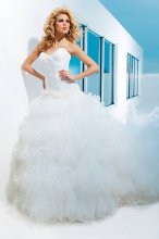 Style No. T112235 Strapless tulle over taffeta ball gown with sweetheart neckline, directionally ruched bodice with dropped waistline and full lace-up corset back, dramatic multi-layered ruffled skirt with lettuce edging and chapel length train. Detachable spaghetti and halter straps included.