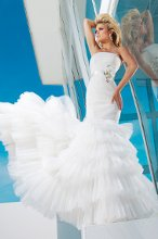 Style No. T112236 Strapless lace and tulle mermaid gown, finely ruched tulle over soft lace bodice with exaggerated dropped waistline features a set in natural waistband adorned with three-dimensional flowers and ribbon with hand-beaded jeweled centers, full lace-up corset back, multi-tiered tulle skirt with chapel length train. Detachable spaghetti and halter straps included.