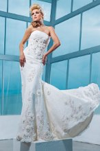 Style No. T112245 Strapless allover soft lace slim A-line gown with ruched Empire bodice, midriff features re-embroidered hand-beaded lace accents and three-dimensional ornamental flower motifs with beaded jeweled centers, matching motifs trail down skirt to chapel length train. Detachable spaghetti and halter straps included.
