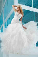 Style No. T112246 Strapless organza and lace ball gown, dramatic deep sweetheart neckline with attached hand-beaded illusion modesty piece, bodice encrusted with elaborate hand-beading and lace appliqués, low dipped back, asymmetrically dropped waistline adorned with side looped bow detail, full multi-layered skirt with scattered beading and chapel length train. Detachable spaghetti and halter straps included.