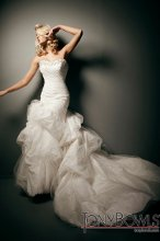 T212273 Strapless taffeta and tulle modified ball gown, softly curved neckline trimmed with jeweled hand-beading, directionally ruched bodice with dramatic asymmetrically dropped waistline and side jeweled motif, full lace-up corset back, multi-tiered pick-up tulle over taffeta skirt with bubble hemline and chapel length train. Detachable spaghetti and halter straps included.