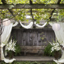 A draped curtain adds a romantic touch to a rustic outdoor space.