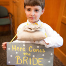 This ring bearer carries a hand-painted sign and burlap ring pillow.