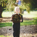 A ring bearer proudly carries his sign.