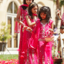 The flowers girls at a bold and bright South Asian wedding.