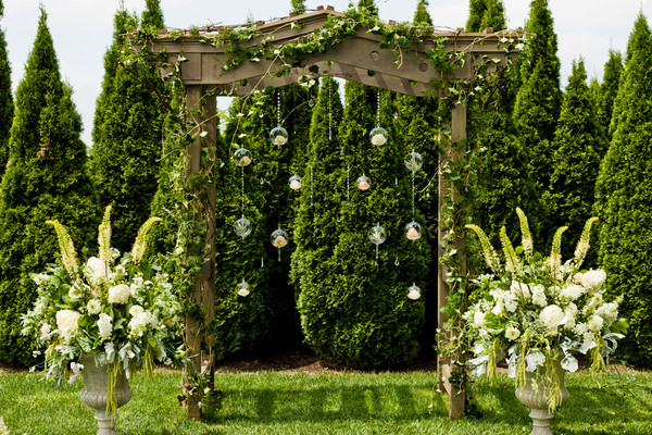 Orbs Of Flowers Create A Unique Backdrop For A Garden Wedding.