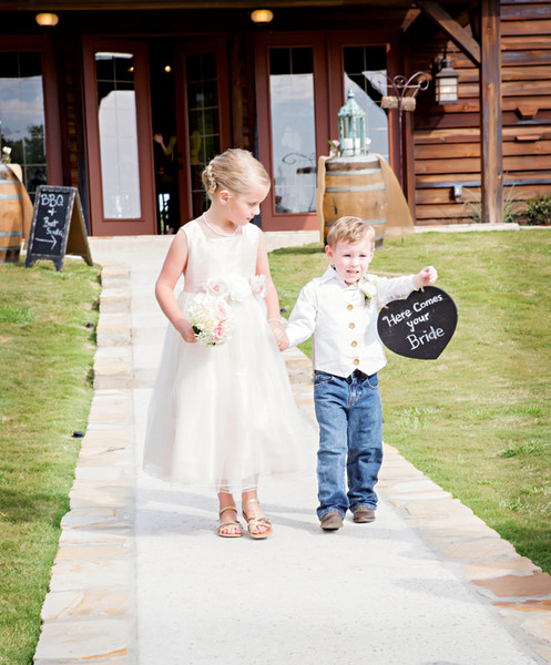 This little duo carry a pretty bouquet and a cheeky sign!