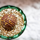 Chocolate truffle topped with golden sprinkles, served in an emerald green goblet.
