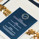 Place setting with dark blue menu card and gold sequin band.