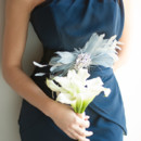 Dark blue bridesmaid dress with feather accents.