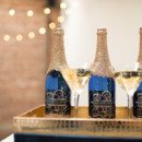 Dark blue champagne bottles with gold glitter detail.