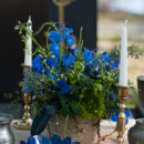 Rustic floral centerpiece featuring blue flowers and greenery.