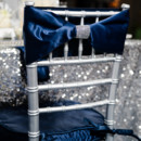 Silver reception chair with dark blue velvet bow.
