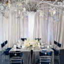Winter wedding reception decor featuring dark blue velvet and tall silver centerpiece.