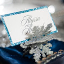 Sparkly blue place card with silver snowflake holder.
